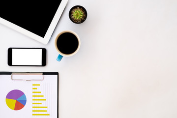 White office desk table with blank screen tablet, chart or graph over backboard, blank screen smartphone and cup of coffee.  Top view with copy space
