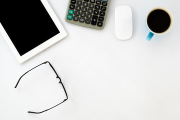 White office desk table with blank screen tablet, mouse, calculator, eyeglasses and cup of coffee. Top view with copy sapce