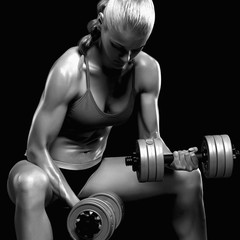 bodybuilder woman with dumbbells.beautiful blonde girl with muscles.gym.monochrome