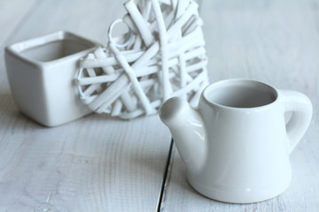 decorative teapot and heart on wooden background.Monochrome