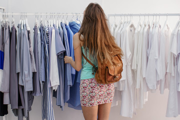 shopping in boutique, the fashionable girl chooses things in shop, an urban style, dressed in a short skirt and a blue t-shirt with a backpack