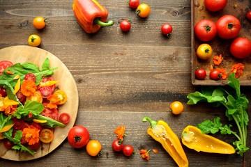 まな板に盛り付けたトマトとルッコラとエディブルフラワーのサラダと食材