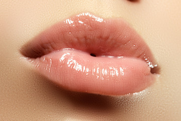 Close-up of a beautiful sexy natural lips giving kiss. Nice full lips with gloss lip makeup. Fashion makeup. Sexy lips. Beauty lips makeup detail