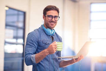 Business executive having coffee and holding a laptop
