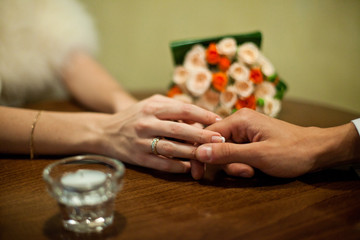 Groom holds bride's fingers tenderly while sitting at the empty