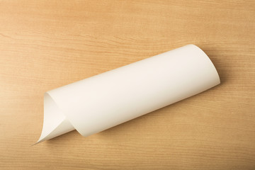 White paper on wood background, rolled up paper