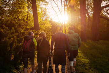 Group of friends walking with backpacks in sunset from back. Adventure, travel, tourism, hike and people friendship concept.