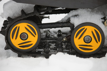 Rollers yellow and black caterpillars of the snowmobile with the