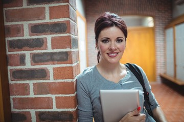 Portrait of mature student holding digital tablet