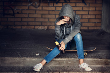 Teen girl holding a beer bottle and smokingon steps