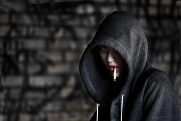 Teen Girl in Hood Smoking a Cigarette