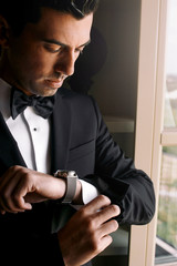 Man in black bow tie looks at his watch while standing in the ro
