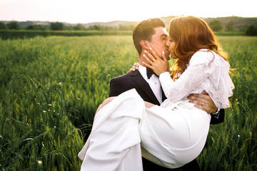 Bride kisses a groom while he carries her through the green fiel