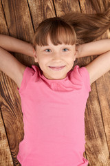 Top view of a smiling little girl lying on back