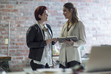 Two women with notebook talking