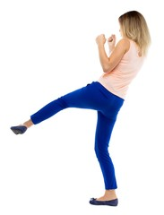 skinny woman funny fights waving his arms and legs. Isolated over white background. The blonde in a pink jacket strikes the right foot.
