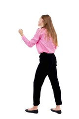 skinny woman funny fights waving his arms and legs. Isolated over white background. Woman office worker in a pink shirt standing in a boxing stance.