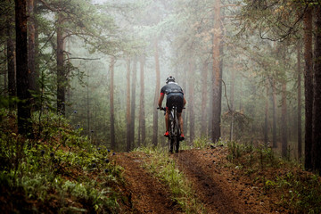 Zelfklevend Fotobehang Fietsen male athlete mountainbiker rides a bicycle along a forest trail. in forest mist, mysterious view