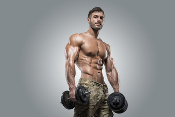Muscular athlete bodybuilder man on a gray background Wall mural