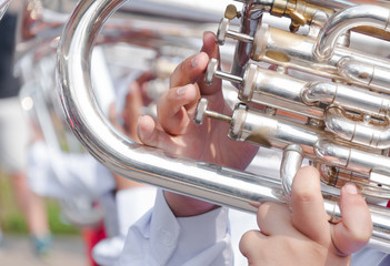 Human hand playing the flugelhorn,fragment of tuba with hands of musician
