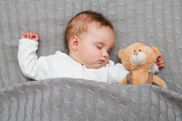 Infant lying on the bed.Baby sleeping with her teddy bear, new family and love concept.