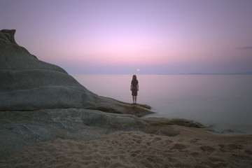 Tranquil seascape scene with girl which looking at the sun