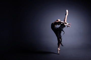 Young ballerina in a black suit is dancing in a dark studio