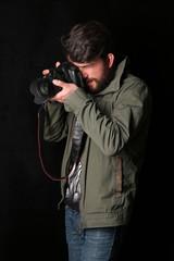 Man wearing khaki jacket takes photo. Close up. Black background