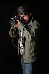 Man dressed in khaki jacket takes picture. Close up. Black background