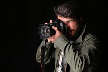 Photographer in khaki jacket takes photo. Close up. Black background