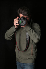 Man inkhaki jacket and jeans takes photo. Close up. Black background