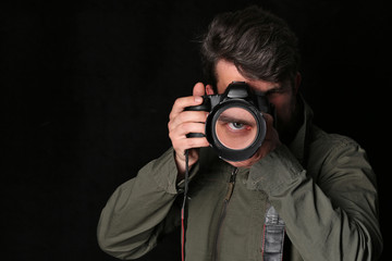 Photographer and his eye in the lens. Close up. Black background