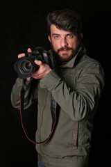 Bearded man with a camera. Close up. Black background