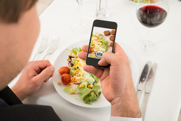 Man Taking Picture Of Food With Mobile Phone