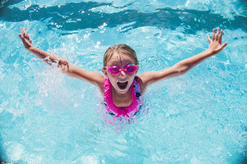 Cheerful girl  in goggles in swimming pool
