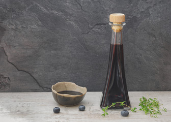 Blueberry vinegar in glass bottle with fresh blueberries and thyme on rustic table.