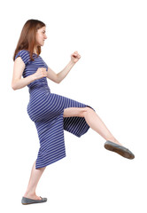 skinny woman funny fights waving his arms and legs. Isolated over white background. The brunette in a blue striped dress in a fighting stance.