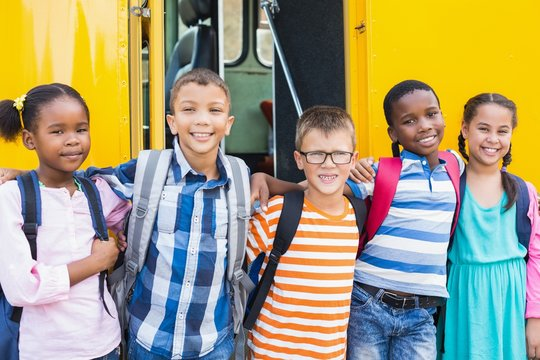 Smiling kids standing arm around in front of school bus