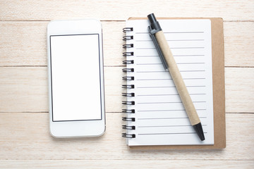 Smart phone, pen and notepad on wooden background close-up