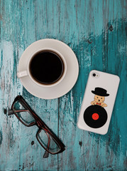 Cup of cofee, glasses and phone on tiffany wood background