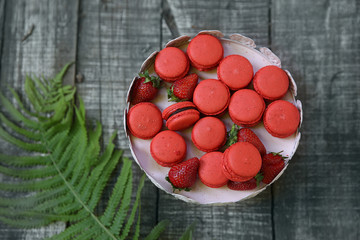 Sweet colorful macaroons with strawberry slices on plate at the wooden floor near a fern leaf