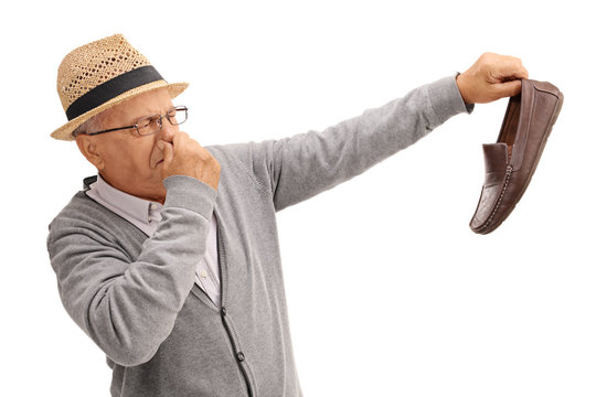 Old man holding a smelly shoe