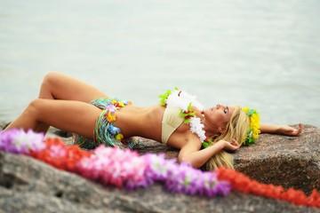 Beautyful hula hawaii girl lie on big stone near sea