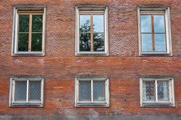 Six casement windows of hard wood, some with grills, placed in the red brick wall of Frederiksberg City Hall in Denmark