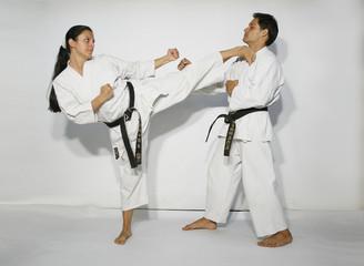 Karate master girl with white kimono black belt does high side kick, kikome geri to the neck of black belt man