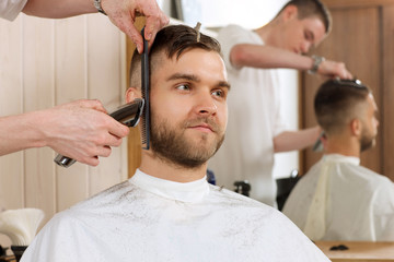 Young bearded man getting beard haircut by hairdresser