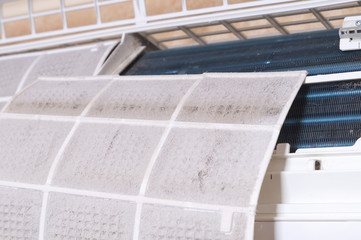 Dirty filter of air conditioner. Cleaning and washing maintenance. Removing dirty air-conditioner filter for washing.