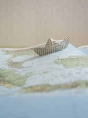 Paper boat on a map book