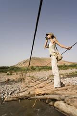femme qui fait des photos sur un pont en bois au dessus d'une rivière