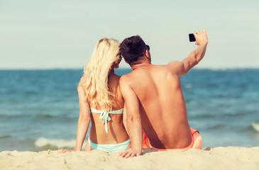 happy couple in swimwear sitting on summer beach